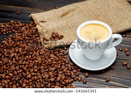 roasted coffee beans and cup on wooden background