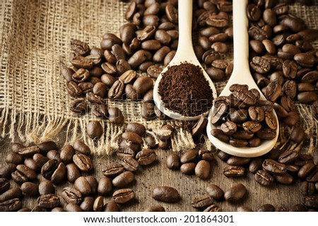 Roasted coffee beans and ground coffee in wooden spoons on coffee heap.