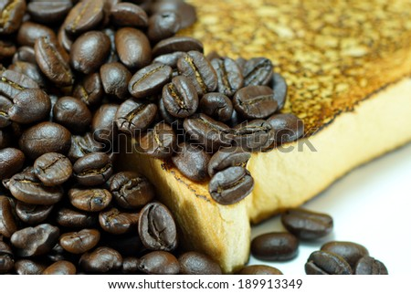Roasted coffee beans and toasted bread slice.