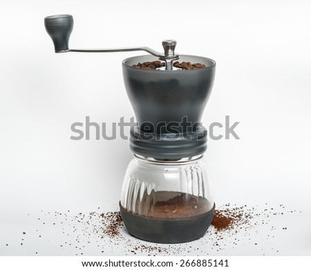 Roasted coffee beans are ground in a coffee grinder, isolated on white background