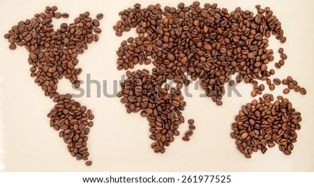 Roasted coffee beans arranged in a world map  on textile background - stock photo