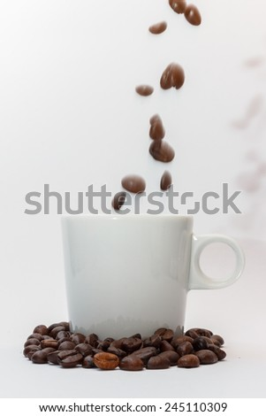 Roasted coffee beans falling into a mug standing in coffee beans isolated on white background - stock photo