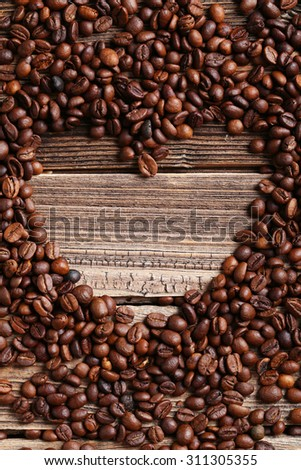Roasted coffee beans heart on a brown wooden background - stock photo