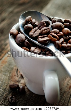 roasted coffee beans in a cup on the table - stock photo