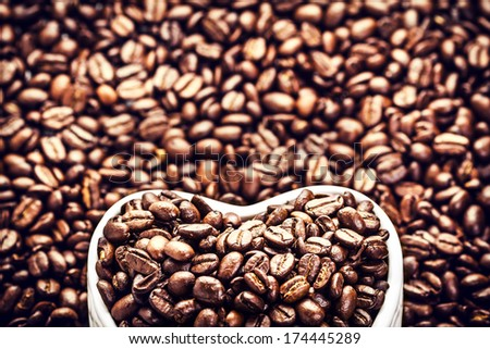 Roasted Coffee Beans in a Heart shaped  bowl at Valentine Day Holiday over coffee beans background macro.  Coffee Beans in Shape of Heart  for Valentine's Day Card.