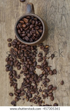 Roasted coffee beans in a plain ceramic mug on a wooden background, top view