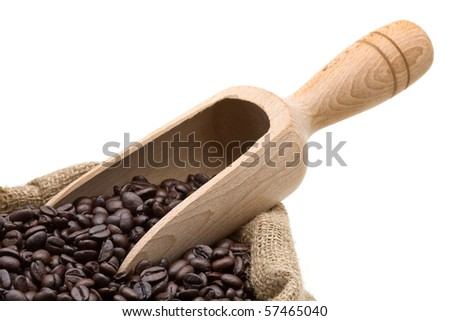 Roasted coffee beans in burlap bag with wooden scoop