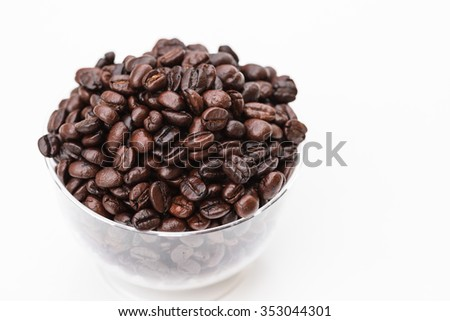 Roasted coffee beans in glassblow on white background