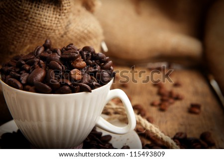 Roasted coffee beans in jute sack and cup on wooden background