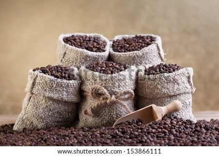 Roasted coffee beans in small burlap bags - on golden background - stock photo