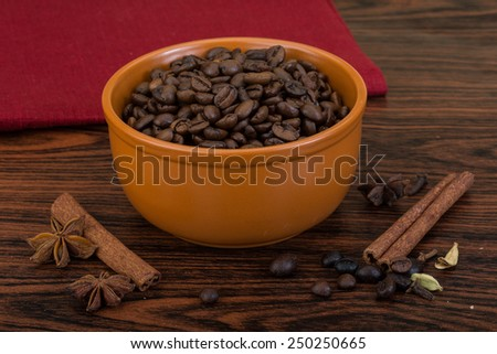 Roasted coffee beans in the bowl with cinamon - stock photo
