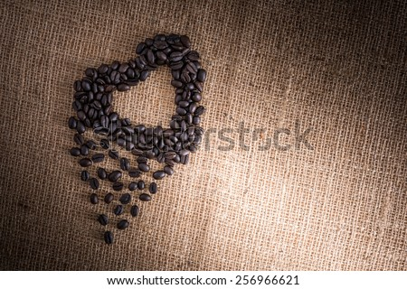 Roasted coffee beans in the shape of a heart.sackcloth is background - stock photo