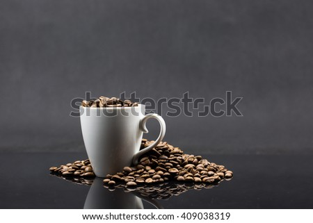 Roasted coffee beans in white cup on black shiny background.