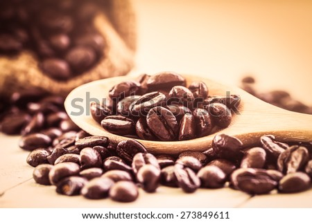Roasted coffee beans in wooden spoon on wooden background in vintage color style - stock photo