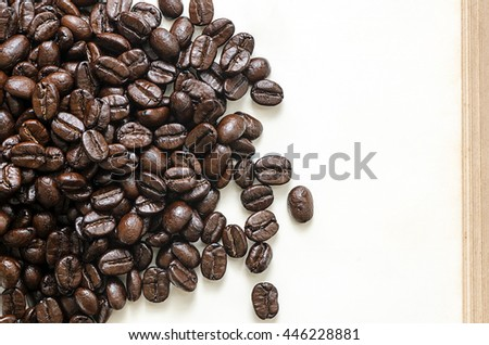 roasted coffee beans on blank page of old book in top view.