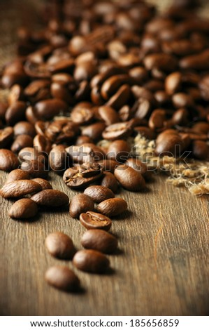 Roasted coffee beans on textured wood. - stock photo