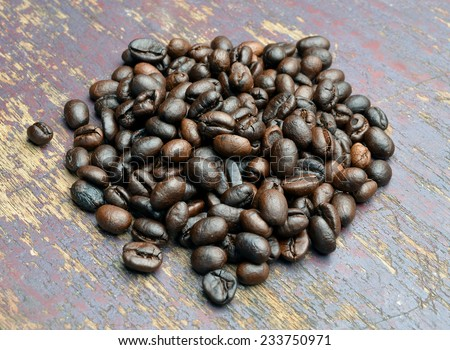 Roasted coffee beans on textured wood.
