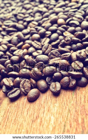 Roasted coffee beans on wooden background with vintage tone. Shallow depth of field. - stock photo