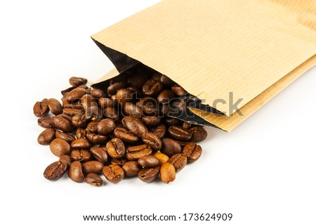 Roasted coffee beans pouring from a craft paper bag on white background - stock photo