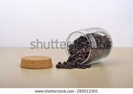 Roasted Coffee Beans Spill Out from Glass Bottle,Selective Focus  - stock photo