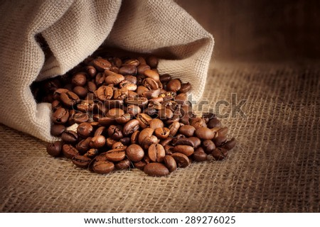 roasted coffee beans spill out of the  background - stock photo