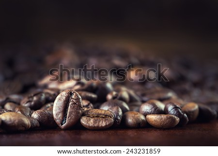 Roasted coffee beans spilled freely on a wooden table.Coffee time   - stock photo