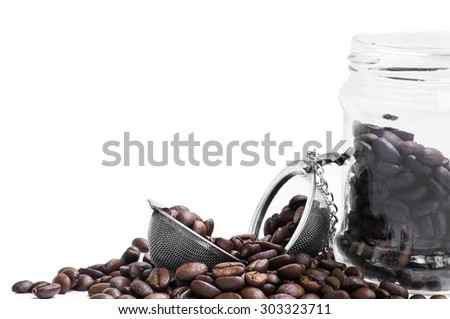 roasted coffee beans, strainer and glass jar - stock photo