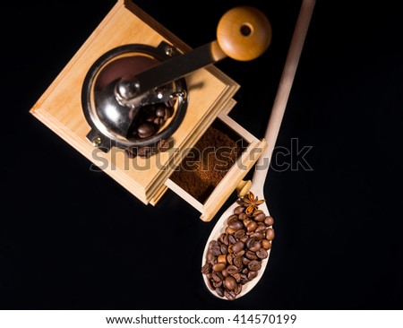 Roasted coffee beans with anise in a wooden spoon near a vintage manual box coffee grinder, isolated close up from high angle with copy space on black - stock photo