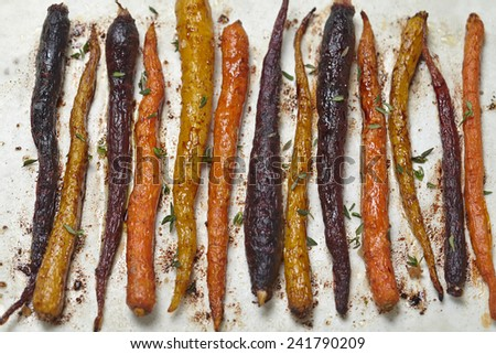 roasted colorful carrots with olive oil and thyme - stock photo