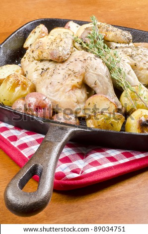 Roasted Cornish Game Hen and Potatoes Garnished with Sprig of Thyme - stock photo