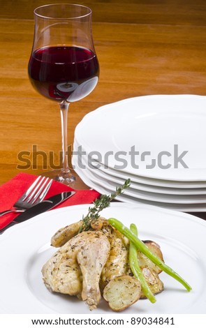 Roasted Cornish Game Hen and Potatoes Garnished with Sprig of Thyme Served with Red Wine - stock photo