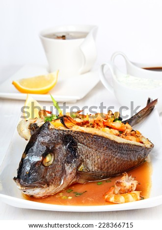 Roasted dorade stuffed with seafood on the white plate. - stock photo