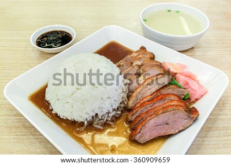Roasted Duck and Red Pork with Rice on White Square Plate Served with Sauce and Soup on Wooden Table - stock photo