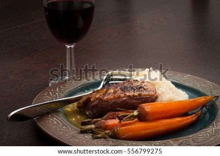 Roasted duck breast in orange sauce with carrots and celeriac mash. Served on a dark wooden table with a glass of red wine.