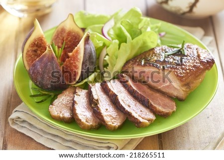 Roasted duck breast with figs, rosemary and salad - stock photo