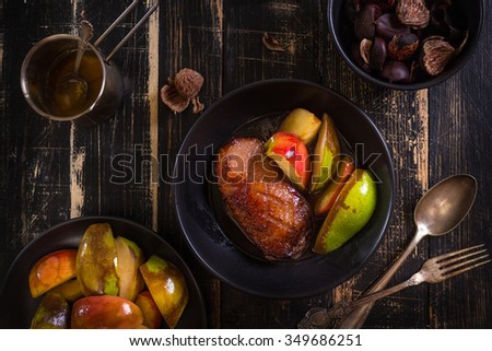 Roasted duck breast with golden crispy skin served with baked apples and chestnuts. Served on a ceramic black plate over rustic dark wooden table. Top view - stock photo