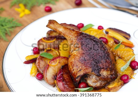 Roasted duck leg with caramelized apples and orange sauce on wooden background - stock photo