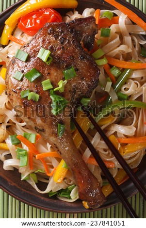 Roasted duck leg with rice noodles on a bamboo table macro. top view vertical