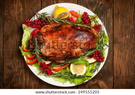 Roasted duck with vegetables, herbs, lemon and berries on wooden table top view