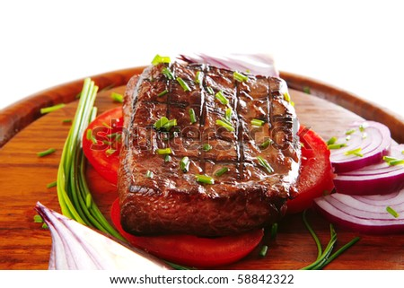 roasted fillet served with tomato on wooden plate - stock photo