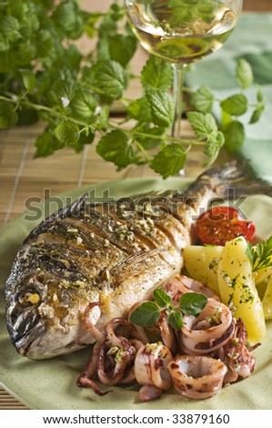 Roasted fish and squid with potatoes close up
