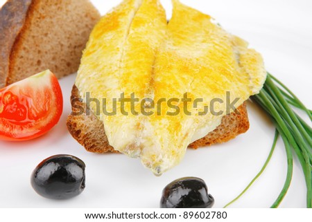 roasted fish fillet with tomatoes,chives and bread on plate over white plate