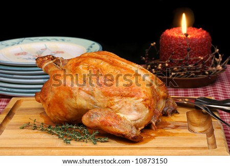 Roasted golden turkey/chicken on carving board in evening setting.