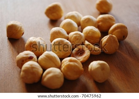 Roasted hazelnuts on natural wooden table background - stock photo