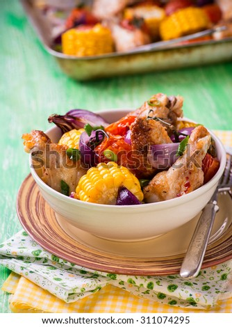 Roasted ?hicken wings, tomato, corn and onion in bowl.  Green background, selective focus, rustic