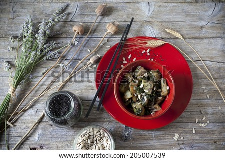 roasted japanese turnips with leaves and seeds on red bowl on rustic background