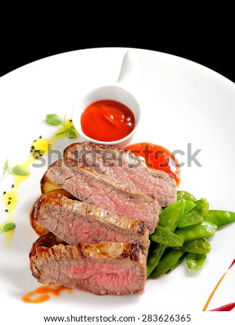 Roasted Kobe Marbled beef fillets with snow peas and tomato sauce - stock photo