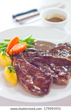 Roasted lamb chops served with fresh carrots, potatoes, beans and brown sauce on big white plate. - stock photo