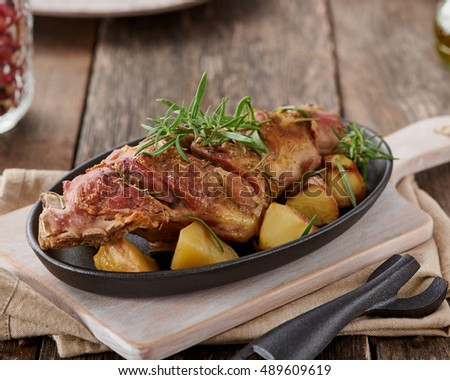 roasted lamb leg with potatoes, rustic style