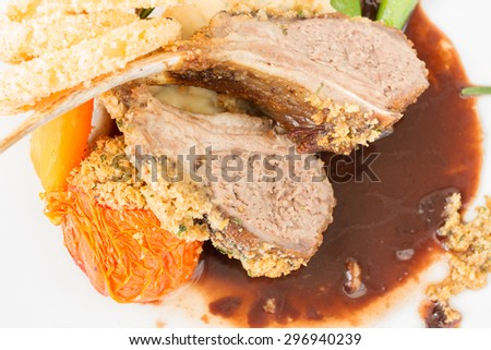 Roasted lamb ribs with onion rings and roasted vegetable - stock photo